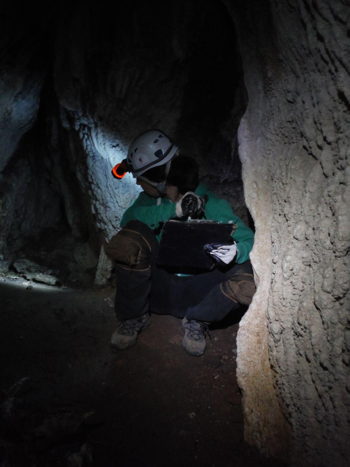 Gloria tomando anotaciones en el interior de la Cueva de La Cabra